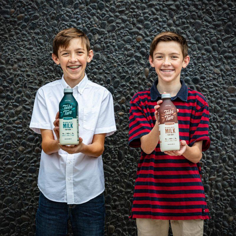 Twins holding Take Two Barley Milk bottles