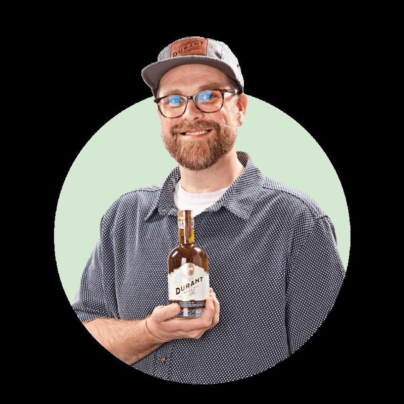 Lee McCollins holding Durant olive oil bottle